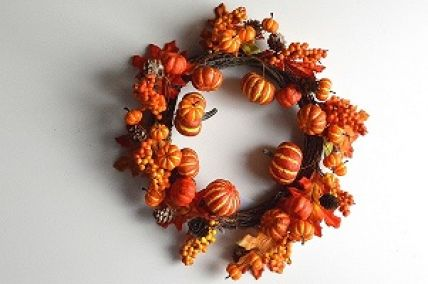 22072 - Autumn/Halloween wreath with an array of golden orange fruits and berries and a scattering of pine cones and bark